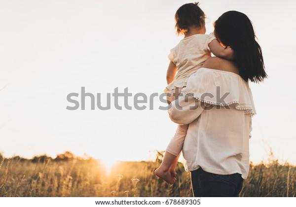 Hintere Sicht auf die kaukasische Brunette Mutter und Kind Tochter umarmen einander auf Wiese Sonnenuntergang. Unten sieht die schöne Brunette-Frau ihr Kleinkind umarmt und auf den Hintergrund der Wiese Sonnenuntergang.