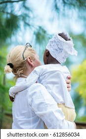 Rear view of Caucasian female doctor holding African black little girl