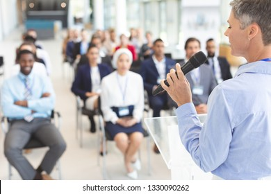 Rear view of  Caucasian female speaker speaks with microphone to diserve business people in a business seminar in a conference room