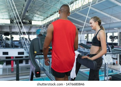Rear view of Caucasian female trainer assisting man to work out on treadmill. Bright modern gym with fit healthy people working out and training