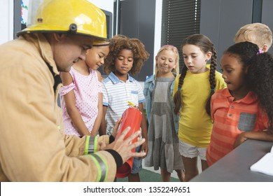 Rear view of a Caucasian firefighter wearing a fire helmet over his head and teaching about fire extinguisher to school kids in classroom at school