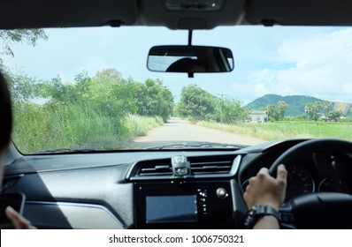 Rear view of Caucasian man driver holding steering wheel.