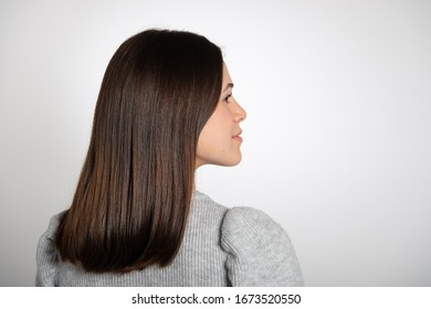Rear view of charming brunette girl looking to the side. Young woman with long brown glossy hair. Isolated on white background.