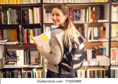 Rear view of charming stylish smiling teenage student girl with backpack standing in the sunny school library in front of the bookshelf with notes in hands while looking at the camera.