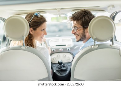 rear view, cheerful couple inside car, looking at each other