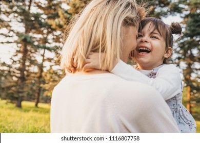 Rear view of cheerful happy girl kid playing with her mother outdoor. Portrait of woman and her cute child laughing in the park outside. Happy emotion. Happy Mother's Day. Motherhood and childhood