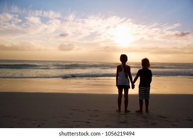 Rear View Of Children Holding Hands Silhouetted On Beach