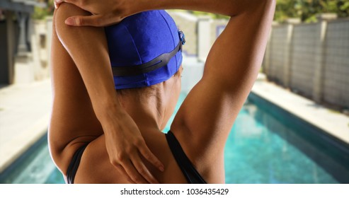 Rear view closeup of black athlete swimmer stretching body before swim