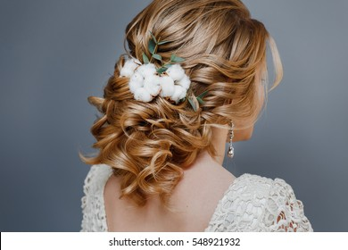 Rear view close-up of the finished wedding hairstyles in the form of winter bride with cotton flowers decoration