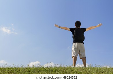 Rear view of a college student with his arms raised while standing outdoors