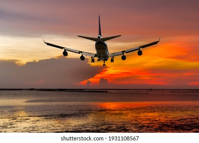 rear view commercial passenger aircraft or cargo transportation airplane fly over coast of sea after takeoff from airport in evening with red sky
