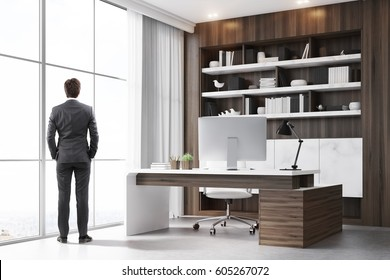 Rear view of a company CEO standing in his dark wood office with a bookcase, a massive table and a computer. 3d renedirng.