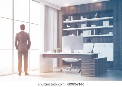 Rear view of a company CEO standing in his dark wood office with a bookcase, a massive table and a computer. 3d renedirng. Toned image