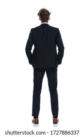 Rear view confident businessman holding both hands in pockets while wearing suit and standing on white studio background