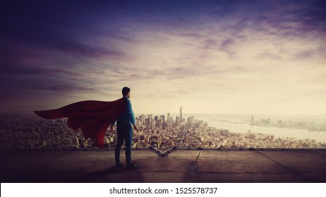 Rear view confident businessman, red cape suit, as hero stands on the rooftop of a skyscraper looking over the city horizon. Superhero leadership and success concept. Surreal super power metaphor.