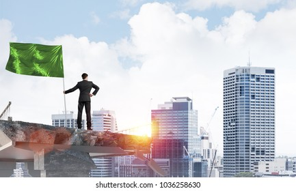 Rear view of confident businessman in suit holding green flag in hand while standing on broken bridge with cityscape and sunlight on background. 3D rendering.