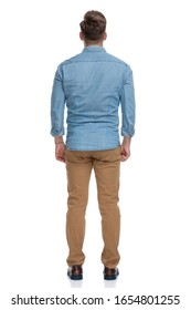 Rear view of a confident casual man standing on white studio background