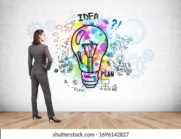 Rear view of confident young businesswoman looking at colorful business idea sketch drawn on concrete wall. Concept of planning