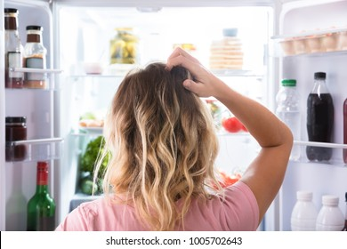 Rear View Of A Confused Woman Looking In Open Refrigerator At Home