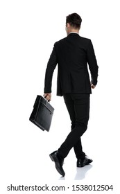 Rear view of a convinced businessman holding a briefcase while wearing a black suit and red tie, moving on white studio background