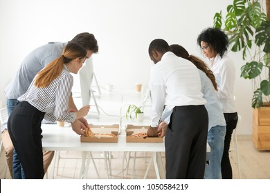 Rear view at corporate employees team sharing pizza in office, multiracial colleagues eating italian food at lunch time, diverse coworkers group taking slices from box on table enjoy meal together
