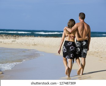 Rear view of couple embracing and walking on beach