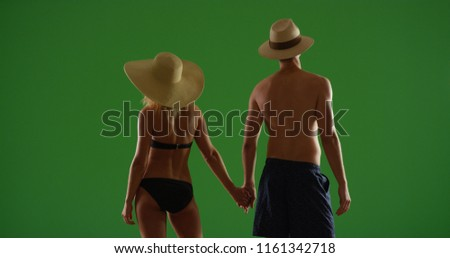 4a65ddb4234f4 Rear view of couple in hats and swimsuits holding hands on green screen