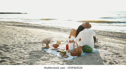 Rear view couple having picnic at the beach, sitting on blanket and embracing, looking to seaview