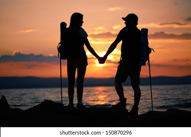 Rear view of couple of hikers holding by hands while standing by water in the evening