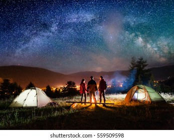 Rear view couple hikers holding hands and their friend stands near campfire and looks at it under night sky with stars on the background mountains and luminous town