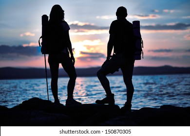 Rear view of couple of hikers standing by water in the evening