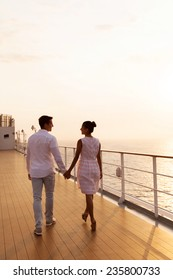 rear view of couple holding hands walking on cruise ship