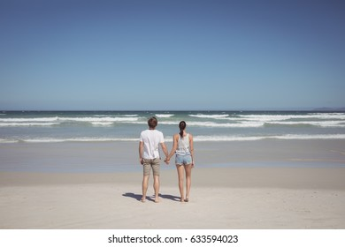Rear view of couple holding hands at beach during sunny day