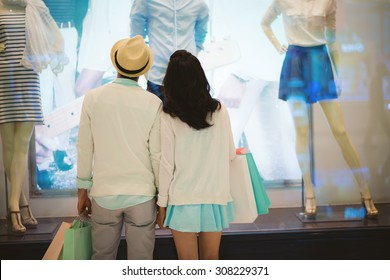 Rear view of couple looking at the clothes in the shop window