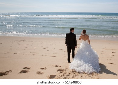 A rear view couple on the beach in wedding dress