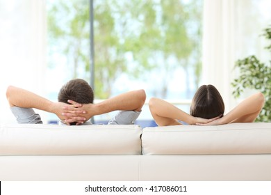Rear view of a couple relaxing on a sofa at home and looking outside a green background through the window of the living room - Shutterstock ID 417086011