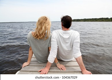 Rear view of couple sitting on a wooden bridge by a lake