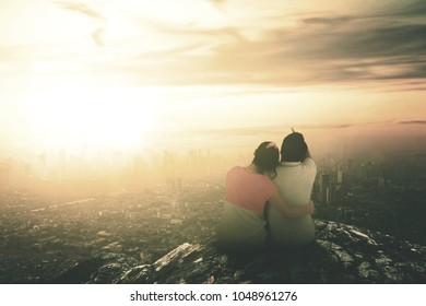 Rear view of couple sitting on top of the mountain to see sunset