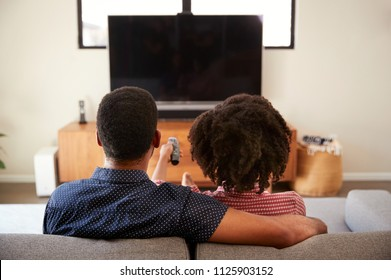 Rear View Of Couple Sitting On Sofa Watching TV Together