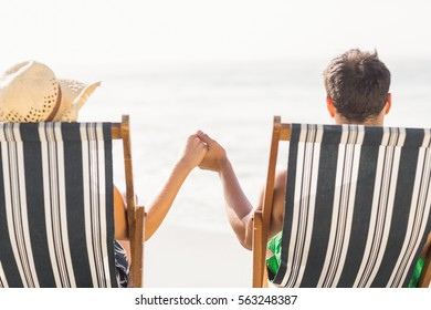 Rear view of couple sitting on armchair and holding hands while relaxing on the beach