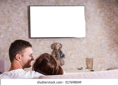 Rear View of Couple Snuggling Together on Sofa While Watching Flat Screen Television Mounted on Living Room Wall, View of Back of Heads on Romantic Date Night - Screen is Blank for Copy