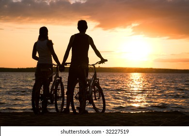 Rear view of couple standing on seashore with their bicycles and enjoying sunset