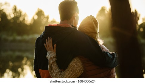 Rear view of couple standing together by the lake. Man and woman in warm clothing looking at a view.
