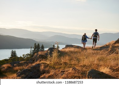 Rear View Of Couple Walking On Top Of Hill On Hike Through Countryside In Lake District UK
