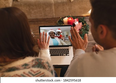 Rear view of couple waving while having a videocall with santa claus and senior woman in santa hat on laptop at home. social distancing during christmas festivity quarantine lockdown concept.