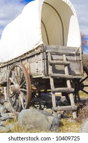 A rear view of a covered wagon used on the Old Oregon Trail. It has  a weathered wooden ladder leaning on it.