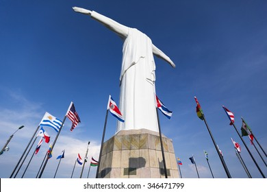 Rear view of Cristo del Rey statue of Cali against a blue sky with international flags waving around. Colombia