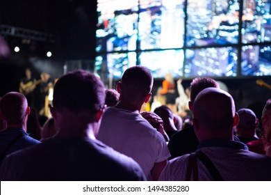 Rear view of crowd with arms outstretched at concert. cheering crowd at rock concert. silhouettes of concert crowd in front of bright stage lights. Crowd at music concert, audience raising hands up