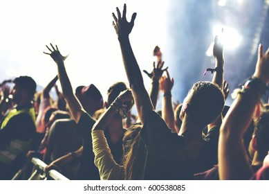 Rear view of crowd with arms outstretched at concert