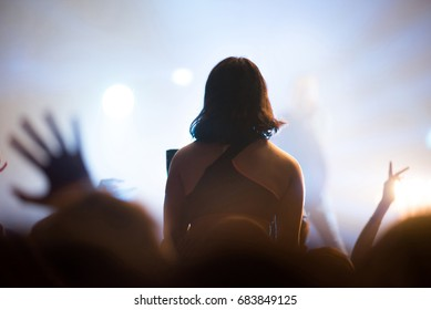 Rear view of crowd with arms outstretched at concert. Bright stage lights in the background